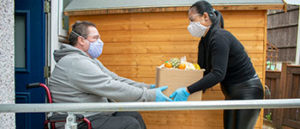 injured man on a wheelchair getting grocery help from an Enliven support worker
